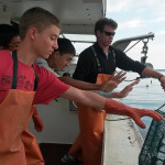 The Boise High School National Ocean Sciences Bowl (NOSB) Team assist a lobsterman returning lobster traps in Casco Bay.