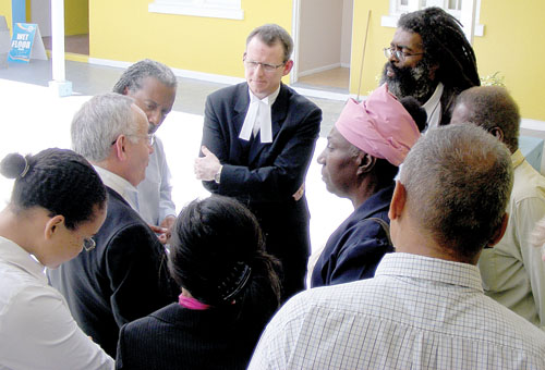Barrister Stephen Hockman, QC, (second from left) and Barrister Mark Beard speak to VIEC members after the first day of the Beef Island development court case. (Photo: Mason Marcus, frontpage of the BVI Beacon, April 30, 2009)